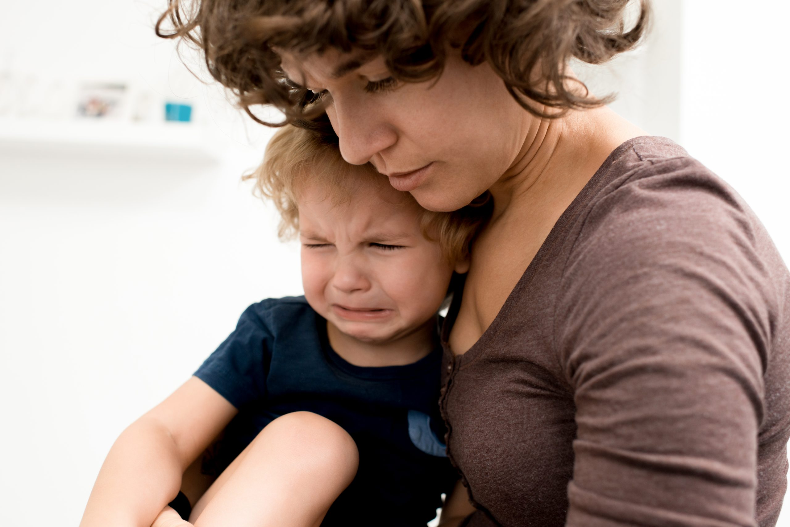 Crying little boy sitting on laps of his beautiful mother while she trying to calm him down, white background