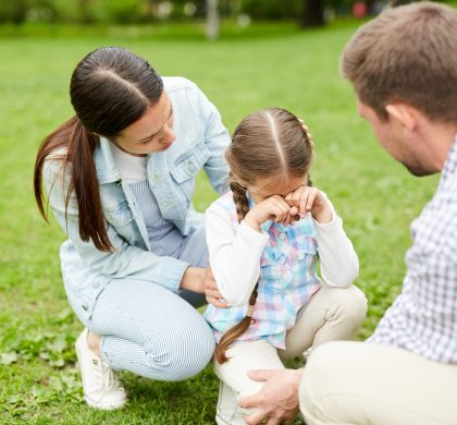 Little girl crying while sitting on grass and her parents comforting her during weekend chill