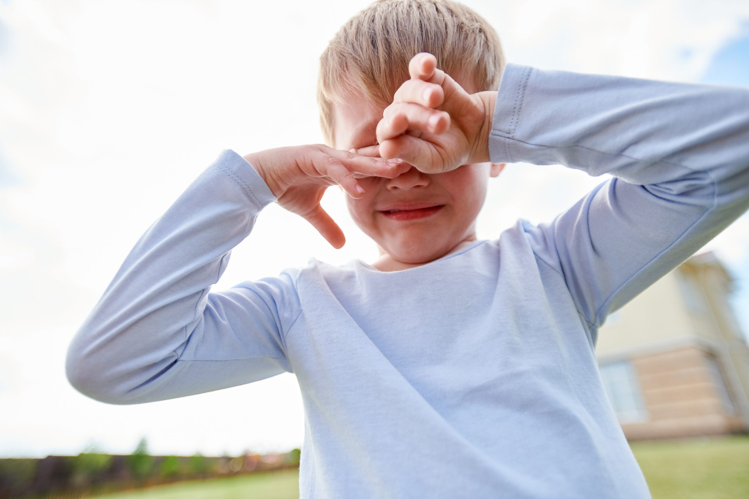 Low angle portrait of sad little boy crying hysterically outdoors, covering eyes with hands