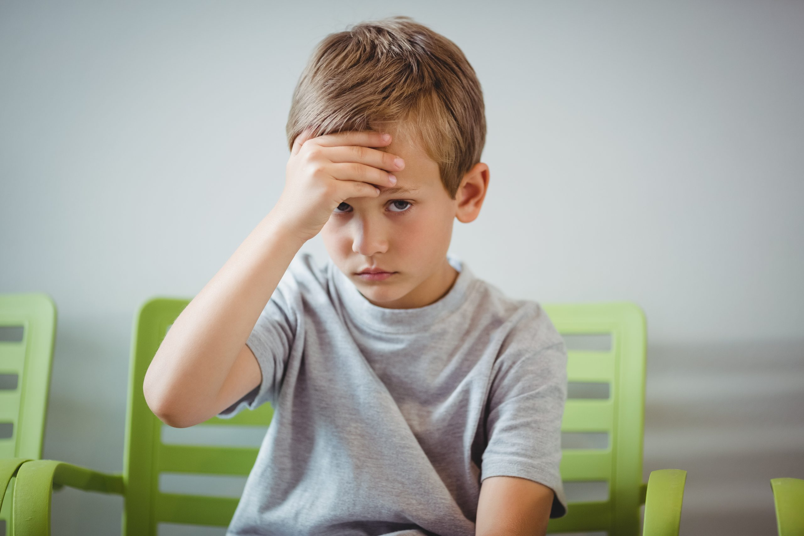 Portrait of upset boy sitting on chair in corridor at hospital