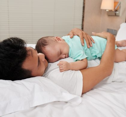Little innocent baby sleeping on chest of his father