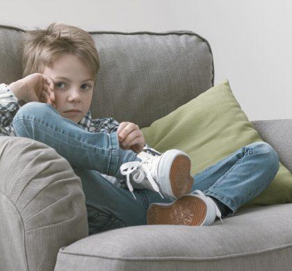Sad boy sitting on an armchair