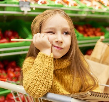 Portrait of bored little girl sitting in shopping cart while waiting for parents to finish buying groceries in supermarket