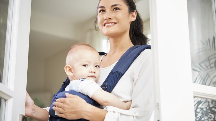 Positive young mixed-race woman carrying baby in sling when opening big window
