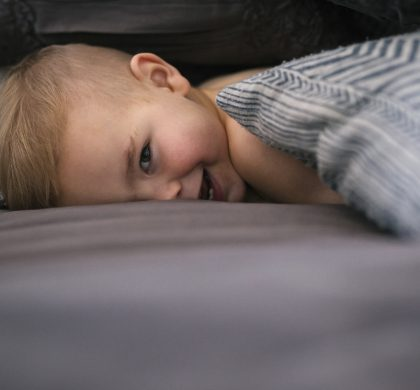 A young boy lying on his stomach in bed looking at the camera and laughing.
