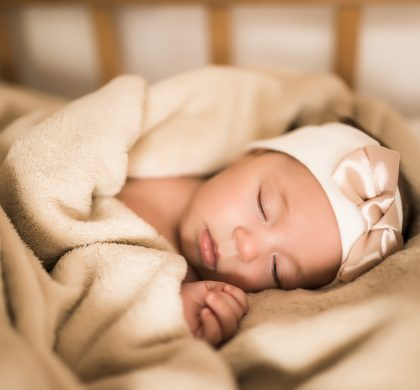 Cute newborn baby with a bandage on his head sleeps sweetly in the wooden crib under a blanket. Little girl sleeping. Light background