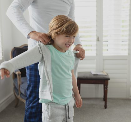 Mid section of Caucasian father helping son putting on clothes in a comfortable home