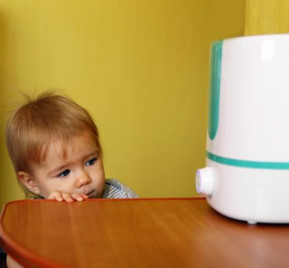 Little girl is looking on a humidifier in bedroom.