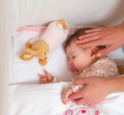 Closeup of mother caressing her cute baby girl sleeping in a cot with pacifier and stuffed toy