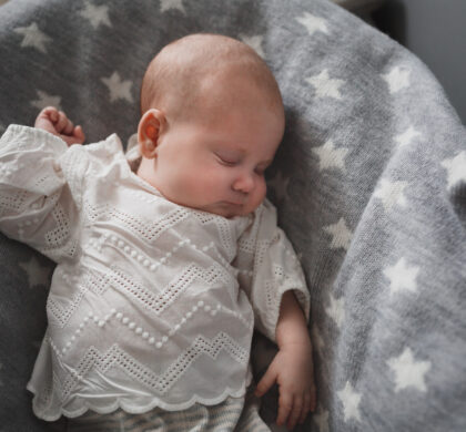 Newborn cute baby in white lace clothes sleeping on a gray bedspread with white stars. Average plan.