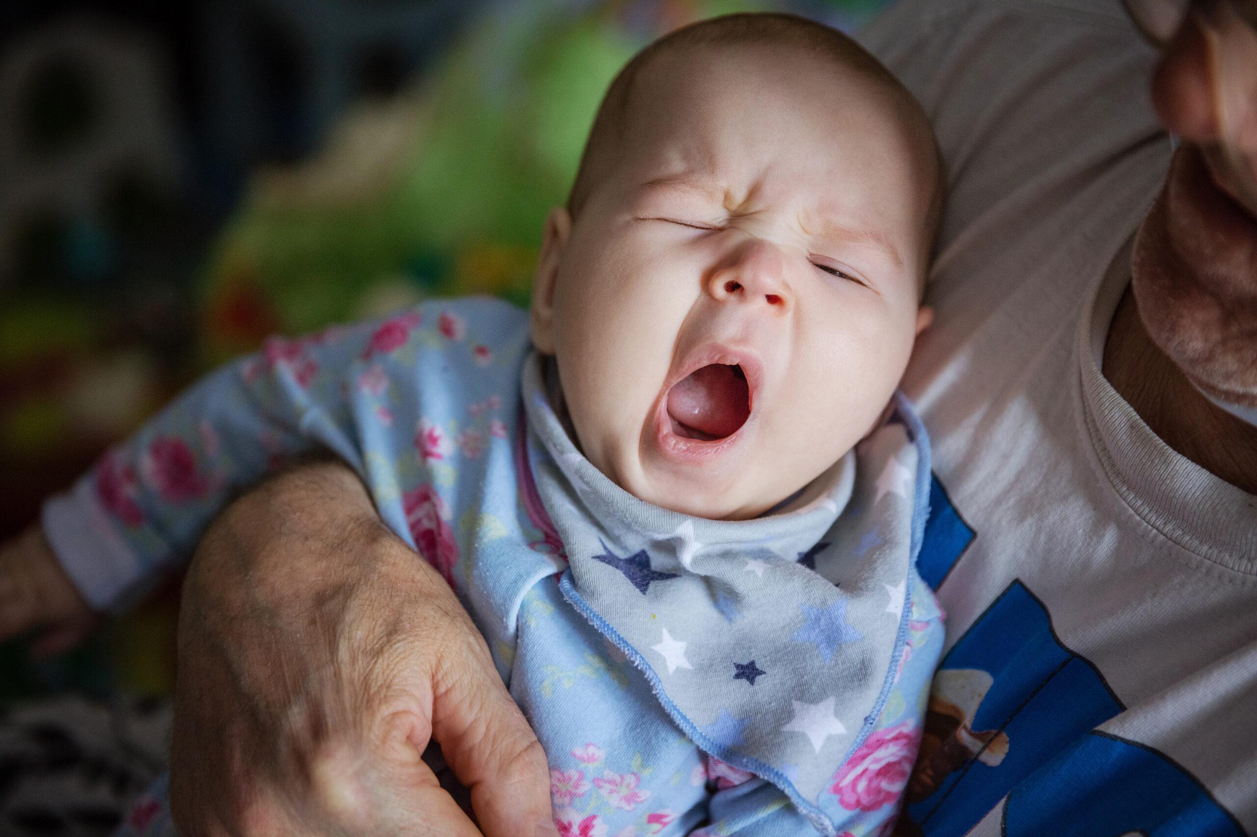 Baby girl yawning. Cropped view of grandfather rocking baby to sleep.