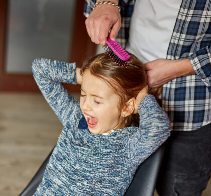 Father combing, brushing his daughter's hair at home, child making faces about hair pulling, angry girl feeling pain, family moments, spending time together.