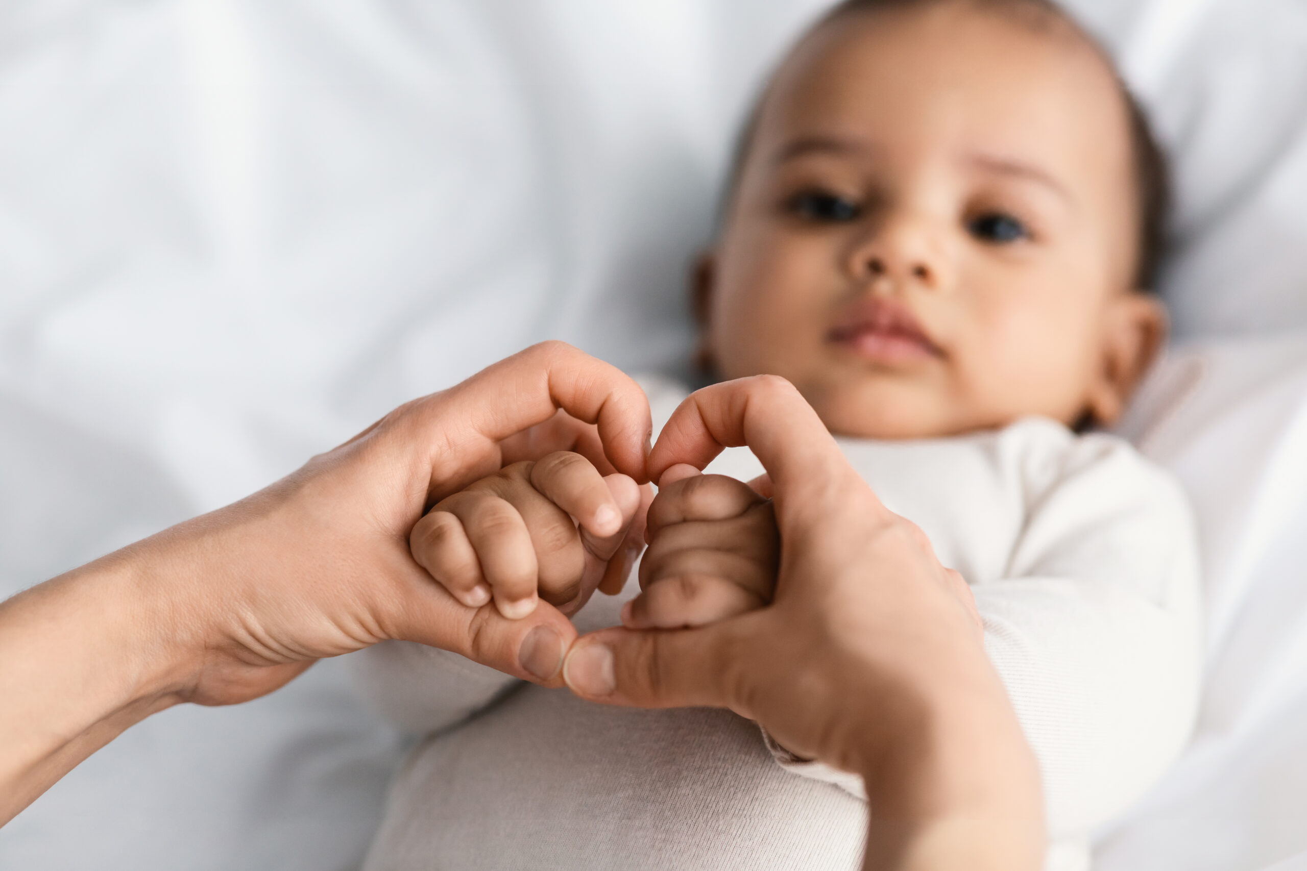 Maternal Love Concept. Closeup of young African American mom holding her cute little baby hands, making heart shape with fingers. Child wearing bodysuit lying on the white blanket sheets at home